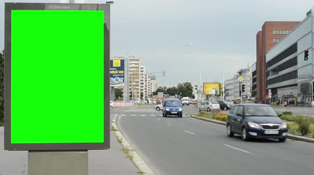 blank : billboard in the city near road - green screen - building,cars and people in background - cloudy sky