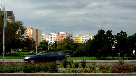 council housing : housing estate (flats) - road with passing cars - nature (trees, grass, bush) in background with people - cloudy sky Stock Footage