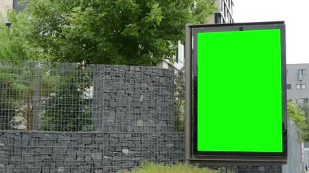 poszter : billboard in the city - green screen - stone fence with trees - building in background