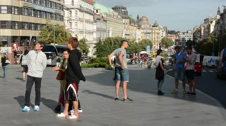 cseh : Wenceslas Square with people and passing cars - buildings and nature(trees and bushes) - blue sky