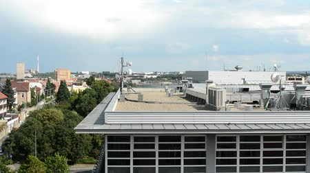 from air : roof of the building - air conditioning and other devices (engine room) - city (buildings in the background) with nature - cloudy sky