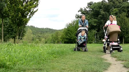 toló : Two women with children in prams walking in the park with little girl on a bike