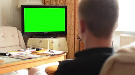 tv screen : Man watches TV(television) - green screen - living room  Stock Footage