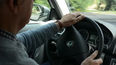 inside car : old man(senior) drives a car - steering wheel Stock Footage