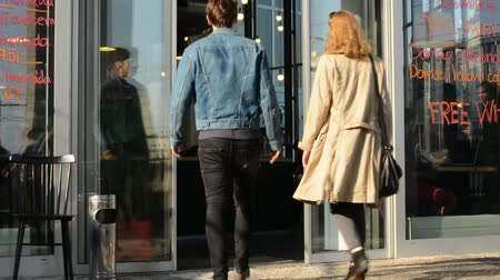 exterior : young couple (man and woman) enter to the building (coffee) - reflection of walking people in the window