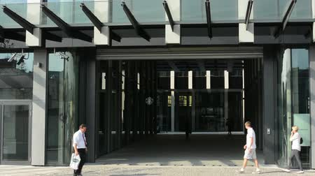 helyek : main entrance to the business office building with people and passing cars
