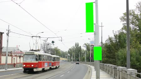 рекламный : billboard in the city near road and buildings - green screen - people with cars and trams