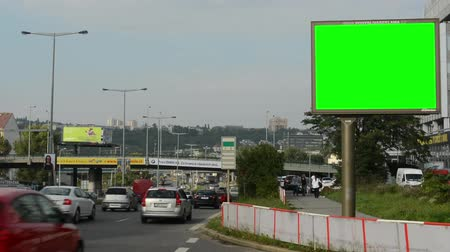 billboard in the city near road and buildings - green screen - people with cars