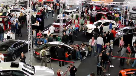 automobilový průmysl : car exhibition - parked cars and people walking and watching cars - timelapse Dostupné videozáznamy