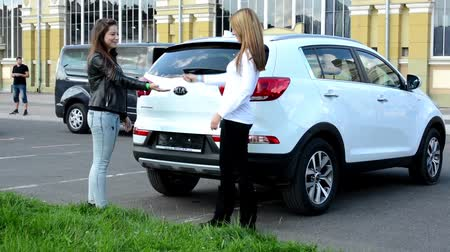 drive : woman (seller) gives keys from the car to customer - test drive Stock Footage