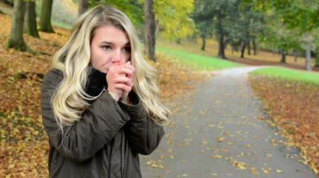 cold : woman shivers with cold - woman gets warmer - autumn park (nature) - woman portrait