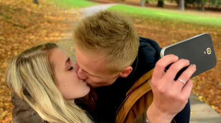 zakochana para : young model couple in love - autumn park(nature) - man and woman are photographing  by smartphone (selfie) - happy couple - couple kiss - closeup Wideo