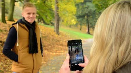 zakochana para : young model couple in love - autumn park(nature) - woman photographing man with smartphone - happy couple - closeup Wideo