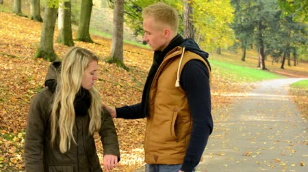 evcil : concept - domestic violence - unhappy couple in autumn park - man grasps womans hand - couple talking (couple arguing)