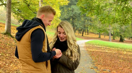 emocional : young model couple in love - autumn park(nature) - couple (man and woman) talking - man gives a gift to woman - happy couple - couple kissing