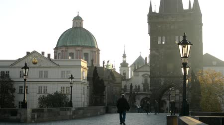 parke taşı : Charles bridge with people walk - sunrise - city - morning mist - buildings with statues - sidewalk cobblestone Stok Video