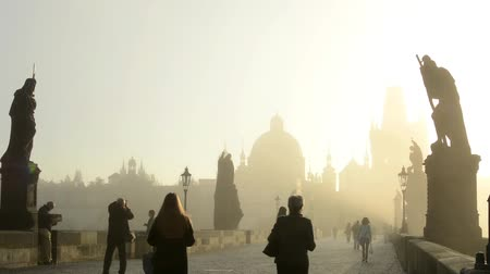 gyalogút : Charles bridge with people walk - sunrise - city - morning mist - buildings with statues - sidewalk cobblestone Stock mozgókép