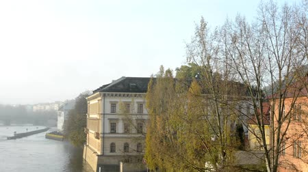 cegła : city - urban buildings with river Vltava - autumn trees - sunrise - sky Wideo
