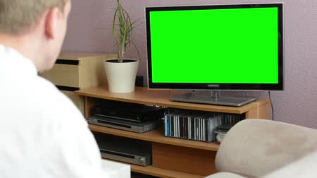 arka görünüm : Man watches TV(television) - green screen