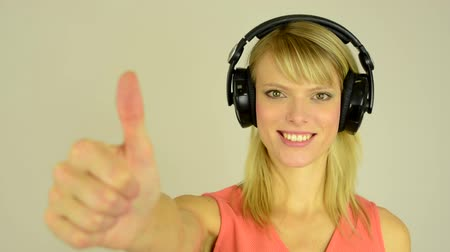 polegar : young attractive woman listens to music with headphones and shows a thumbs up to the agreement - studio - closeup