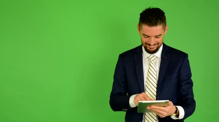 homem de negócios : business man works on tablet and smiles - green screen - studio Vídeos