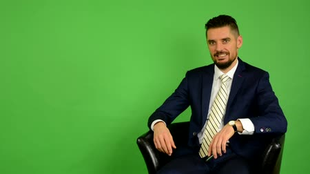 стоять : business man sits and phone and smiles - green screen - studio