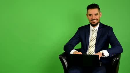notebooklar : business man sits and works on notebook and smiles - green screen - studio