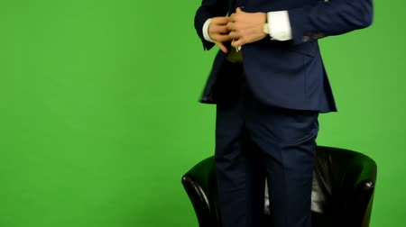 стулья : business man sits and waits (looks at watch) and leaves - green screen - studio