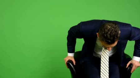 aşağı bakıyor : business man goes to sit down and smiles - green screen - studio