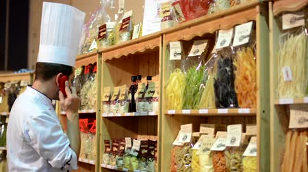 paketleme : chef phone in front of colourful pasta (olive oil, flour etc.) in bags in shelf - shop