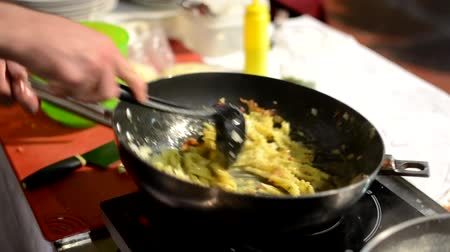 preparing : chef prepares food - chef cook pasta on frying pan - add cheese to pasta