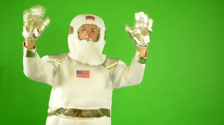 astronaut waves with both hands - green screen