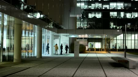 entrance : modern building and group of people leave the building office - quitting time