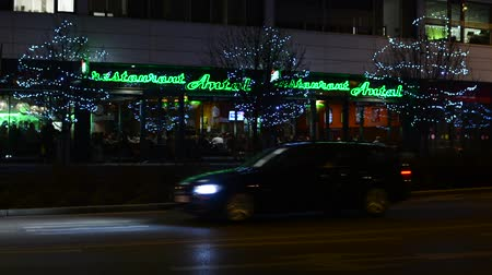 night scene : restaurant exterior with people - city: urban street with cars - urban trees decorated with christmas lights - night