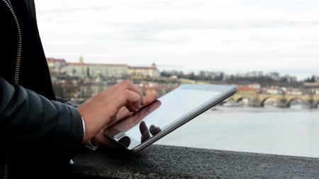 prague bridge : woman works on tablet on the bridge - city (Prague) and river in background - closeup (shot on hand)