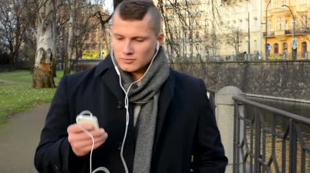 walking man : young handsome man walking and listens music on smartphone - city
