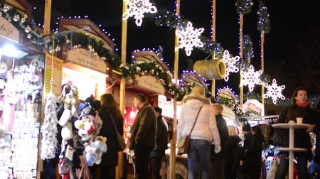bazar : Christmas marketplace (shops) with people - decorations - building in background Vídeos
