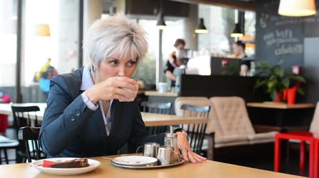 stáří : business middle aged woman drinks coffee in cafe Dostupné videozáznamy