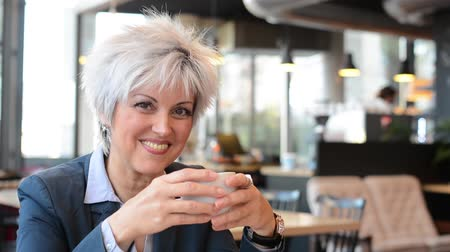 orta : business middle aged woman drinks coffee in cafe and smiles to camera - closeup Stok Video