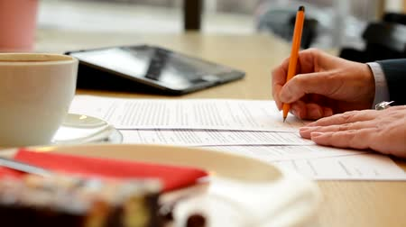 anlaşma : middle aged woman signs a contract (signature) in cafe - coffee with cake and tablet