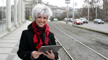 stáří : middle aged woman works on tablet - urban street with cars in the city
