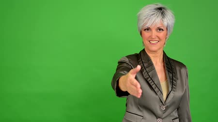 dát : business middle aged woman gives a hand in greeting and smiles - green screen - studio Dostupné videozáznamy