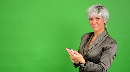 orta : business middle aged woman works on phone and smiles - green screen - studio