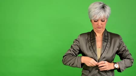 üzleti öltöny : business middle aged woman adjusts clothing - green screen - studio - closeup Stock mozgókép