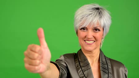 polegar : business middle aged woman shows thumb on agreement - green screen - studio - closeup Vídeos