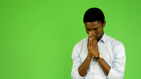 multikulturális : young handsome black man prays - green screen - studio