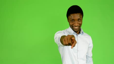 dedo humano : young handsome black man points to camera - green screen - studio Stock Footage