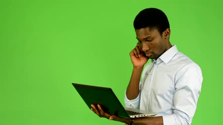 elszigetelt fekete : young handsome black man works on notebook and phone - green screen - studio Stock mozgókép