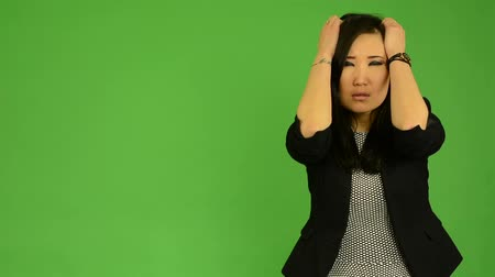 caos : young attractive asian woman is afraid - green screen studio