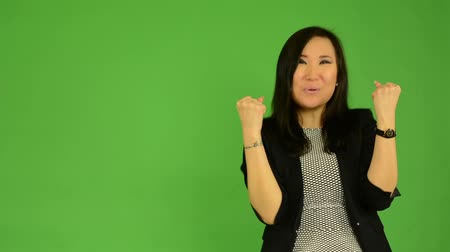 igen : young attractive asian woman rejoices - green screen studio